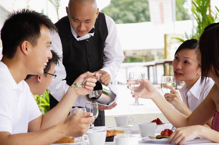 Group of friends having lunch, waiter pouring water at their table Stock Photo