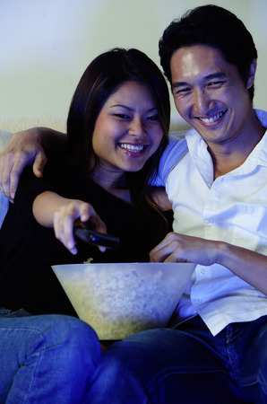 pareja viendo tv: Couple watching TV, woman holding remote control