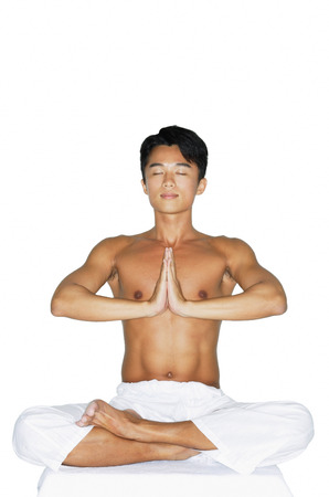 Man practicing yoga, hands together