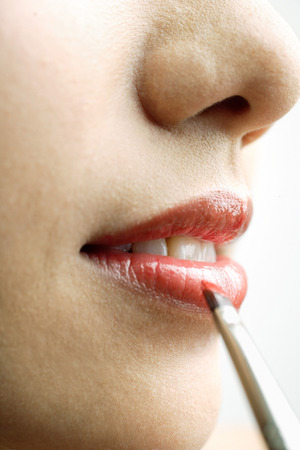 Close up of womans mouth, putting on lipstick with lip brush