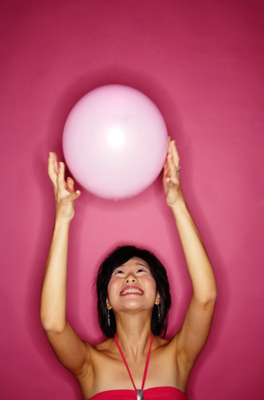 tossing: Woman tossing pink balloon LANG_EVOIMAGES