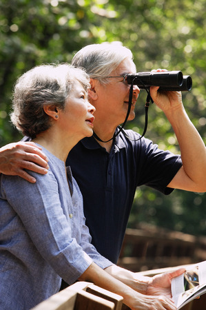 using binoculars: Senior couple side by side, man using binoculars LANG_EVOIMAGES