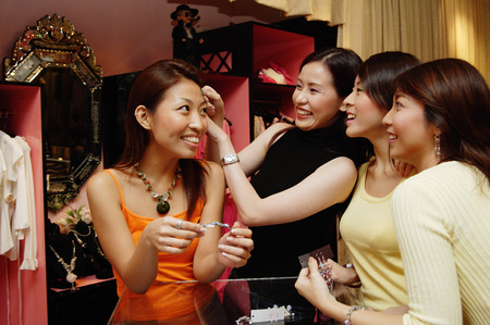 womans clothing: Women at clothing store, one woman putting hair clip on another womans head, others watching