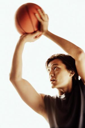 Man aiming basketball, looking away Stok Fotoğraf