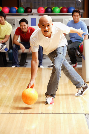 Man aiming bowling bowl, friends in the background, watching Banco de Imagens - 69310192