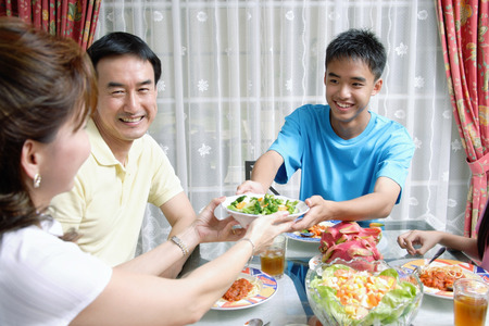 Mother and son passing food to each other at dining table