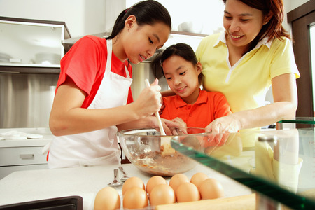 Mother and two daughters in kitchen