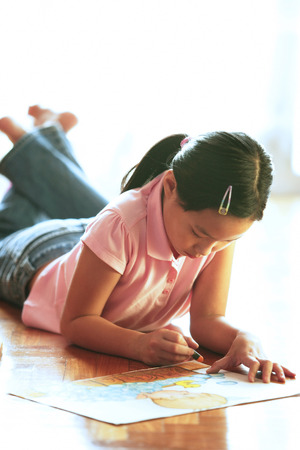 Girl lying on floor, drawing with crayons