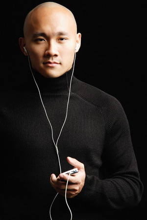 Man with shaved head, listening to music with earphones, looking at camera