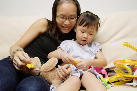 3 4 years: Mother and daughter on sofa, playing with toys