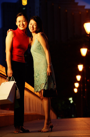 Two women standing, arms around each other, smiling at camera Banco de Imagens