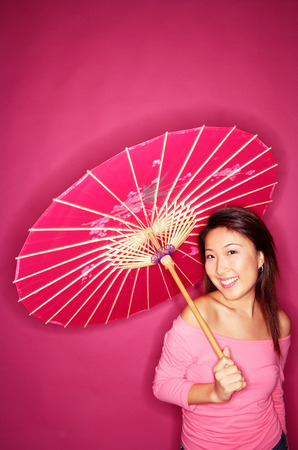 Woman holding umbrella, wearing pink top, standing against pink background Stock Photo