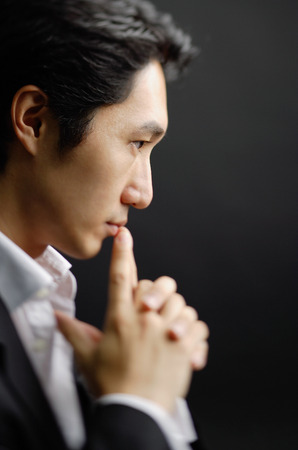 Man with clasped hands, fingers on mouth
