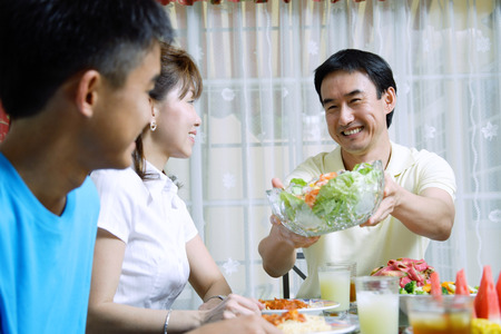 Father passing salad bowl to family members Stock Photo