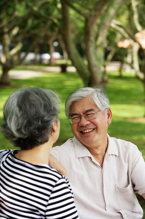 Mature couple sitting in park, facing each other, man smiling