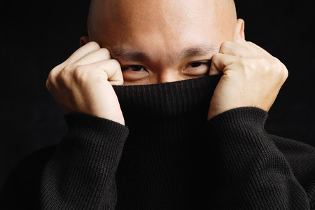 Man hiding behind turtleneck Stock Photo