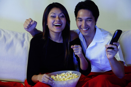 Couple watching TV, making fists, smiling Stok Fotoğraf