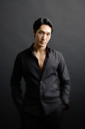 metrosexual: Man dressed in black, standing against black background, hands in pocket