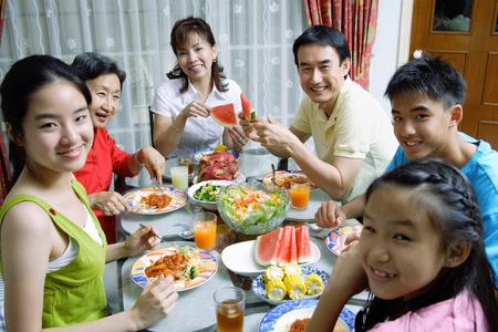 three generation: Three generation family around dining table, looking at camera