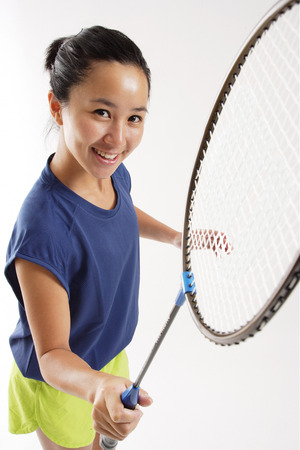 vietnamese ethnicity: Woman holding badminton racket, smiling up at camera LANG_EVOIMAGES