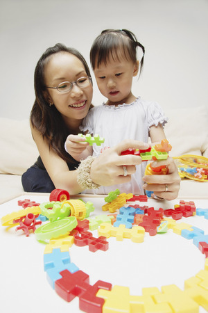 3 4 years: Mother and daughter playing with puzzle pieces