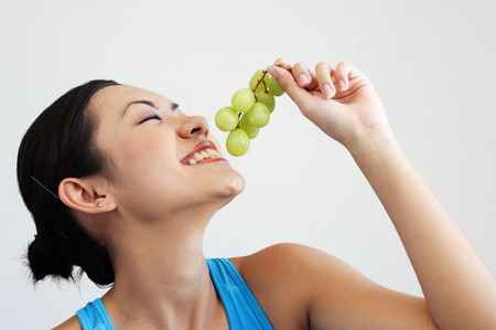 side view: Woman holding grapes near mouth, side view