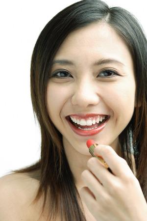 Woman smiling at camera, putting on lipstick Stock Photo