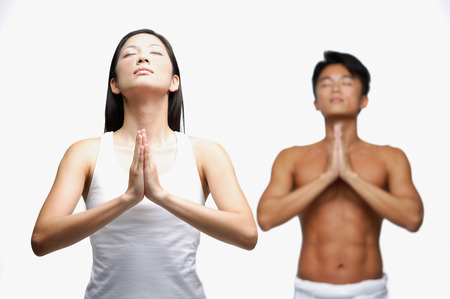 Couple doing yoga, woman in front, man standing in background Stock Photo