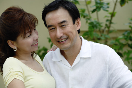 Man smiling at camera, woman smiling at man