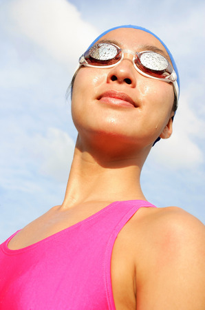 Woman wearing swimming goggles, smiling, looking away, head shot Stock Photo