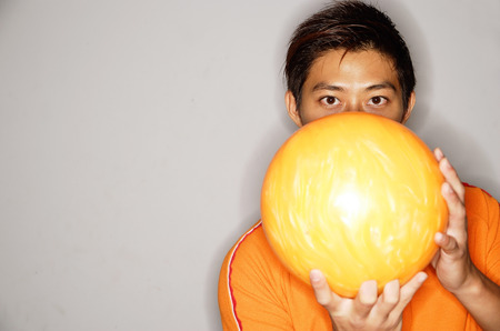 Man holding bowling ball in front of face