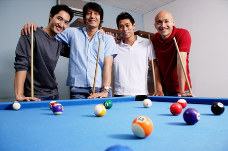 Men standing around pool table, looking at camera