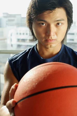 perspiring: Man holding basketball, looking at camera