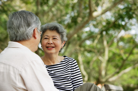 Mature couple facing each other, woman smiling