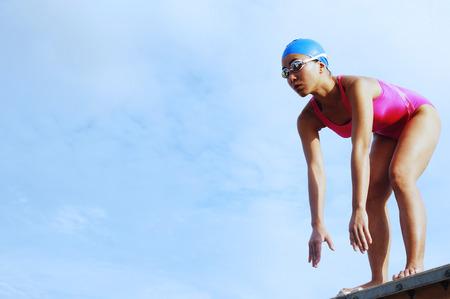 bending: Woman in swimming costume, bending over, preparing to dive