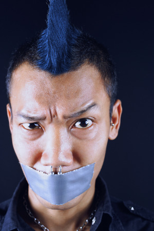 Man with mohawk, mouth taped shut, looking at camera, eyebrow raised