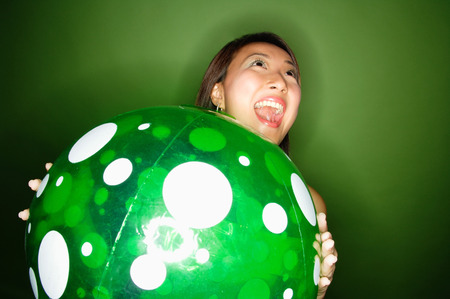 Woman holding inflatable ball, mouth open LANG_EVOIMAGES