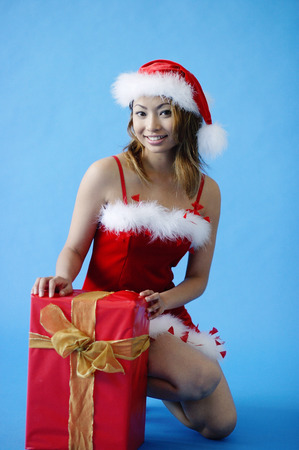 Woman in Santa hat, crouching next to gift box