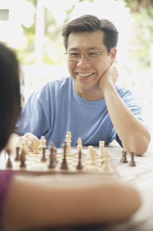 Father playing a game of chess with daughter Banco de Imagens