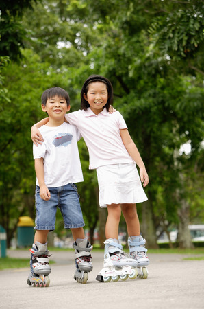 blading: Children on rollerblades, arms around each other LANG_EVOIMAGES