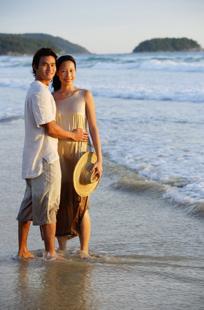 ankle deep in water: Couple standing on beach, ankle deep in water, looking at camera LANG_EVOIMAGES