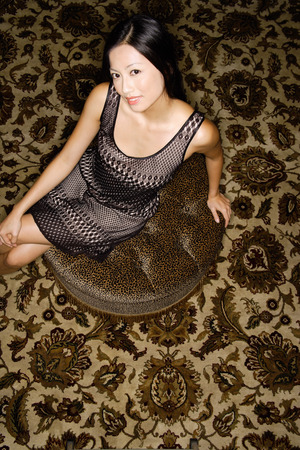 Woman sitting on oriental carpet, looking at camera LANG_EVOIMAGES