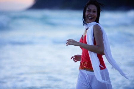 Woman in red top and white scarf, running along beach, smiling