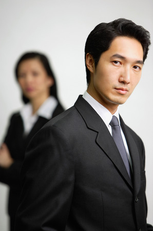 business: Businessman looking at camera, woman in the  background