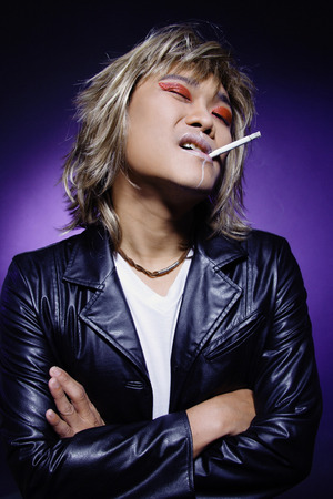 crossed cigarette: Man in leather jacket, wearing make-up, cigarette in mouth