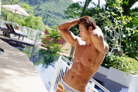 Man in swimming trunks, hands on head