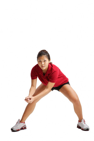 Young woman bending down, waiting for volleyball LANG_EVOIMAGES