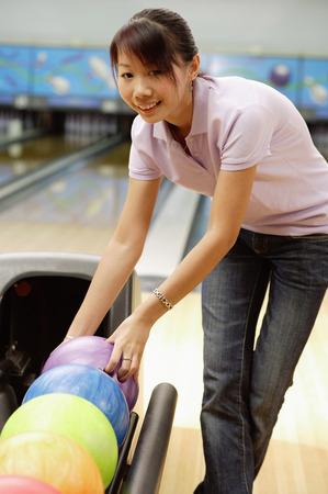Woman selecting ball at bowling alley Stock Photo