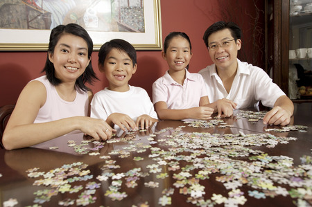 top 7: Family of four in living room working on jigsaw puzzle LANG_EVOIMAGES
