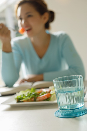 focus in foreground: Young woman eating salad, focus on the foreground
